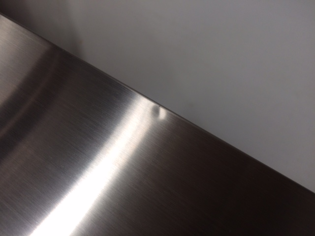 There is a small dent on the top of the fridge along the back edge.